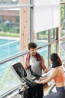 Istruttore di fitness parlando al cliente