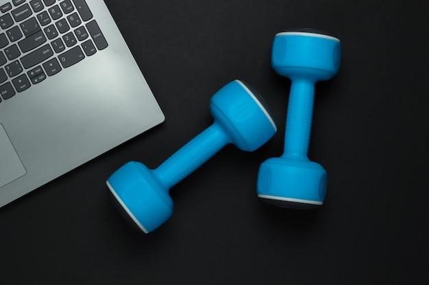 Concetto di fitness. formazione online per una professione di coaching. laptop, manubrio su sfondo nero. vista dall'alto