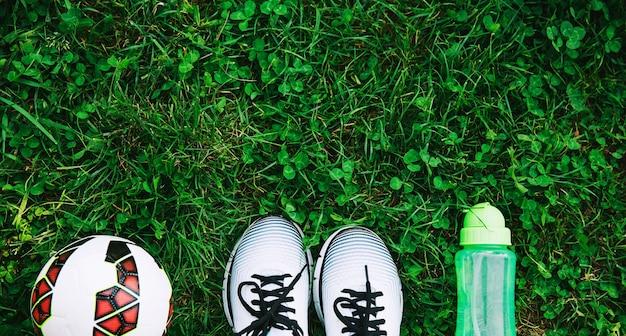 Concetto di fitness scarpe da ginnastica scarpe da ginnastica palla e bottiglia d'acqua su un'erba verde fresca