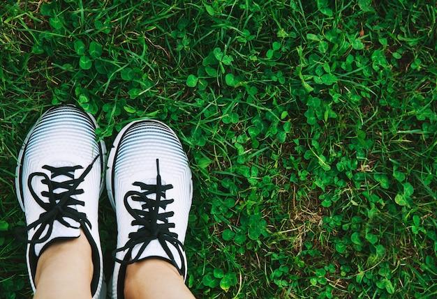 Concetto di forma fisica. scarpe da ginnastica scarpe sportive su un prato verde fresco. vista dall'alto di attrezzature sportive.