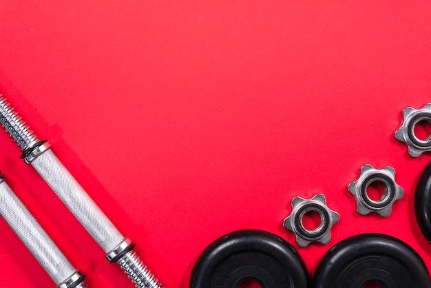 Concetto di forma fisica con attrezzatura da palestra su rosso
