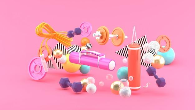 Attrezzature per il fitness in mezzo a palline colorate su uno spazio rosa