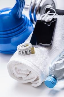 Attrezzature per il fitness. kettlebell asciugamano manubri acqua smart phone con cuffie e metro a nastro.