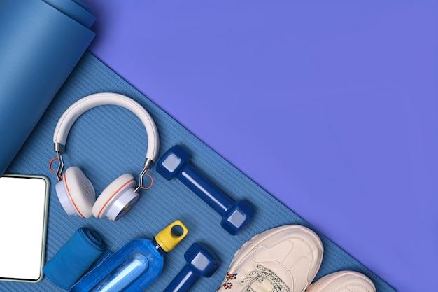 Attrezzature per il fitness e smartphone sul tappetino blu.