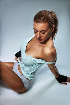 Concetto di moda fitness. bella ragazza con una figura sportiva perfetta in posa sulla macchina fotografica. muscoli addominali ideali. copia spazio.