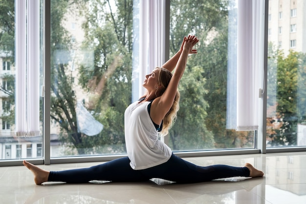 L'istruttore femminile di forma fisica pratica lo yoga per la schiena sana vicino alle finestre in palestra