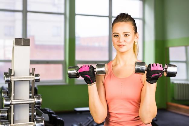 Donna femminile di forma fisica che fa il suo allenamento con le teste di legno in palestra