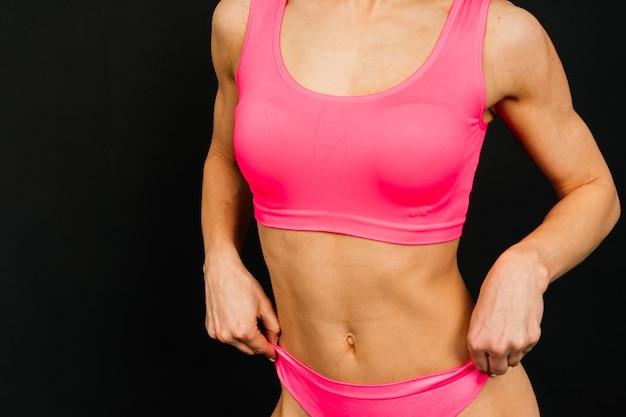 Fitness donna femminile con il corpo muscoloso, fare il suo allenamento. attraente corpo femminile allenato