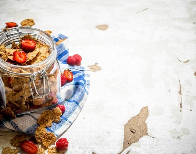 Cibo fitness. muesli con frutti di bosco in un barattolo sul tessuto. su fondo rustico.