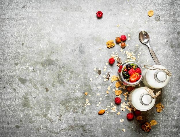 Cibo fitness. muesli con frutti di bosco, noci e latte in bottiglia. sul tavolo di pietra.