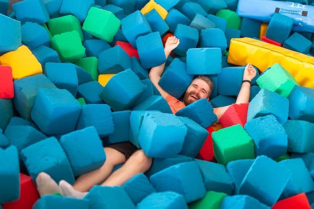 Concetto di attività fitness, divertimento, tempo libero e sport - uomo felice divertente divertendosi su un trampolino al chiuso