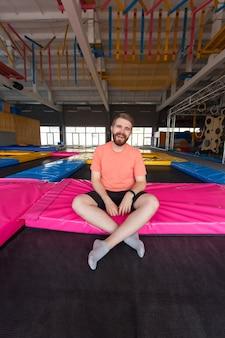 Concetto di attività fitness, divertimento, tempo libero e sport - uomo seduto su un trampolino al chiuso.