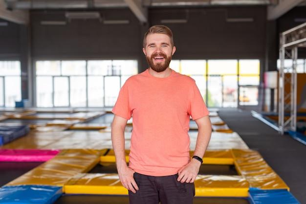 Concetto di attività di fitness, divertimento, tempo libero e sport - uomo sorridente su un trampolino al chiuso