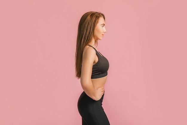 Ragazza di forma fisica che sorride in abiti sportivi neri su una superficie rosa