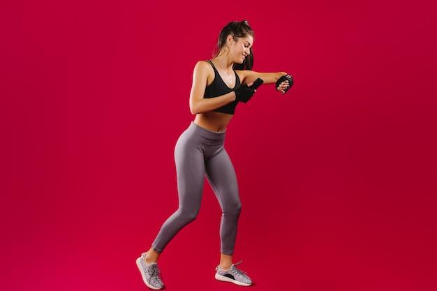 Ragazza di forma fisica in abbigliamento sportivo durante l'allenamento osserva i suoi risultati su un braccialetto fitness e uno smartphone