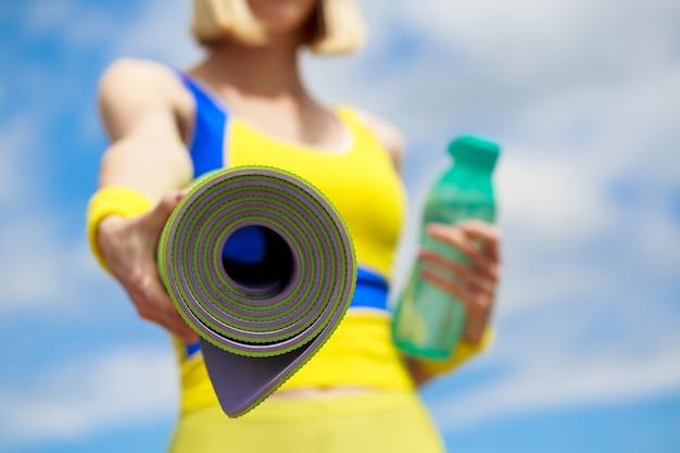 Ragazza di forma fisica con materassino yoga su sfondo cielo. la donna in abbigliamento sportivo sta tenendo una stuoia di yoga e una bottiglia d'acqua.