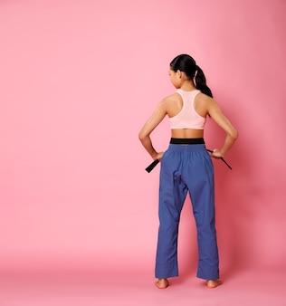 Ragazza fitness, la donna può fare il concetto. a tutta lunghezza 12 anni atleta donna indossa abbigliamento sportivo color pastello e gira la vista posteriore su sfondo rosa, copia spazio