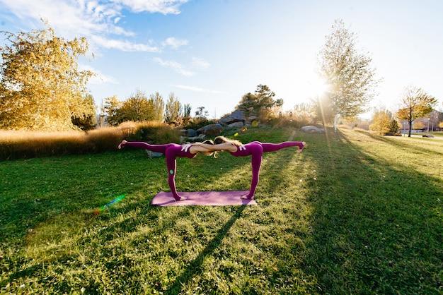 Gruppo fitness facendo yoga nel parco posa. allenarsi.