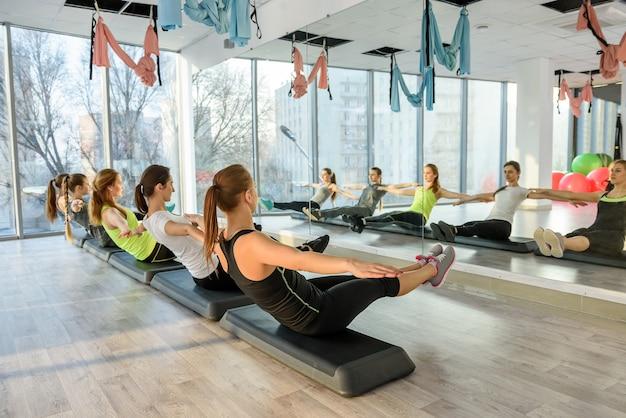 Gruppo di fitness che allena i muscoli della pancia in palestra