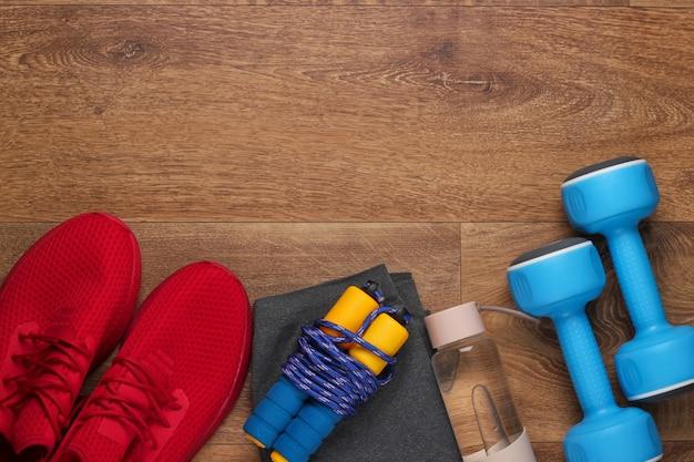Fitness, concetto di stile di vita sano. scarpe sportive rosse, manubri, bottiglia d'acqua, corda per saltare sul pavimento. vista dall'alto