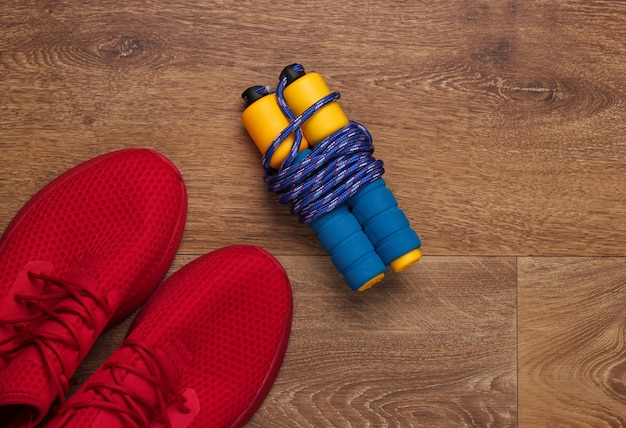 Fitness, concetto di stile di vita sano. scarpe sportive rosse, corda per saltare sul pavimento. vista dall'alto