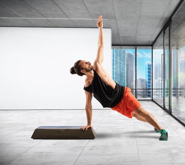 Istruttore di fitness in equilibrio sul gradino