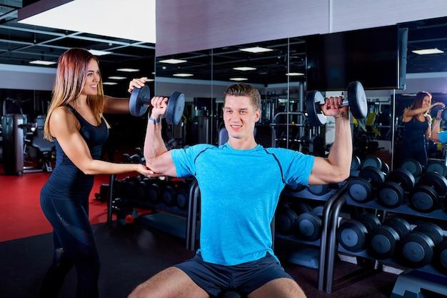 Donna istruttore di fitness che si esercita con il suo cliente in palestra