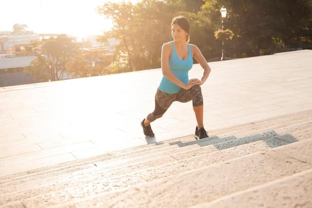 Concetto di fitness e stile di vita - donna che fa sport all'aperto.