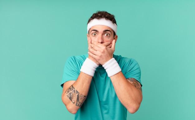 Uomo di forma fisica che copre la bocca con le mani con un'espressione scioccata e sorpresa, mantenendo un segreto o dicendo oops