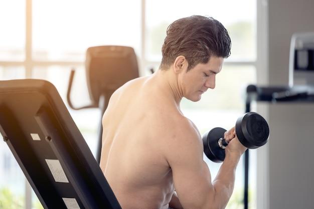 Uomo di forma fisica che fa esercizio con manubri