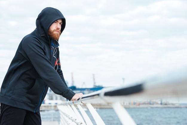 Uomo di forma fisica che guarda lontano vicino al mare