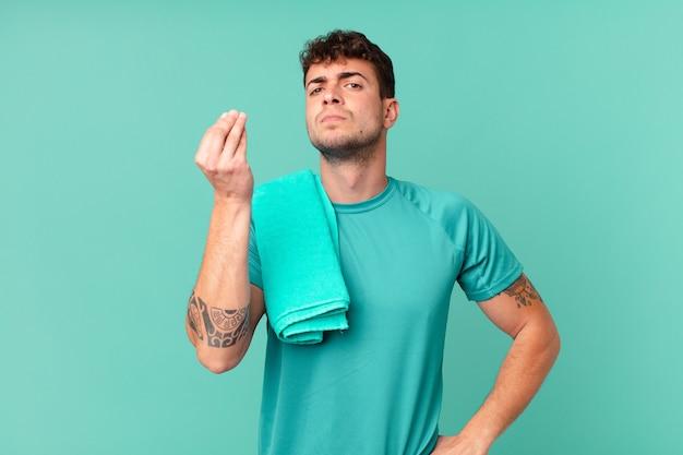 Uomo di forma fisica che fa un gesto di denaro o di denaro, dicendoti di pagare i tuoi debiti!