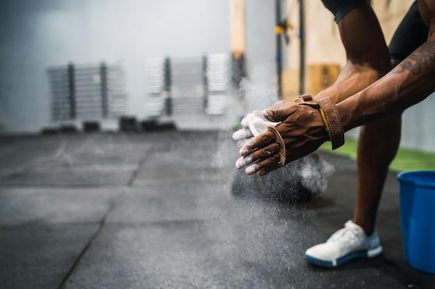 Mani di sfregamento dell'uomo di forma fisica con polvere di magnesio del gesso.