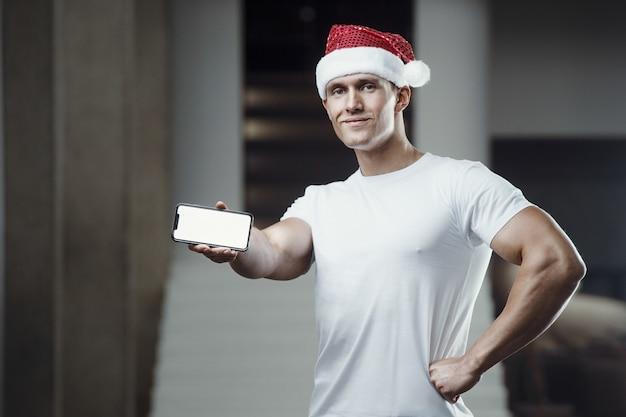 Uomo di forma fisica in costume del cappello di babbo natale in palestra con il telefono cellulare.