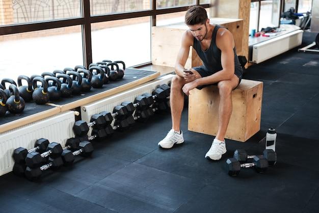 L'uomo fitness si siede sulla scatola in palestra