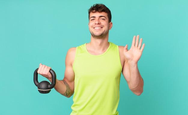 Uomo di forma fisica che sorride allegramente e allegramente, agitando la mano, accogliendoti e salutandoti, o salutandoti