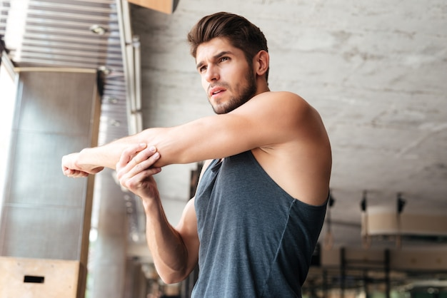 Uomo di forma fisica in fase di riscaldamento in palestra. guardando lontano