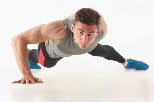 L'uomo di forma fisica che strizza dal pavimento dimostra buoni esercizi fisici isolati su sfondo bianco stile di vita sano per molte persone che esercitano il proprio peso per perdere per ogni giorno push up.