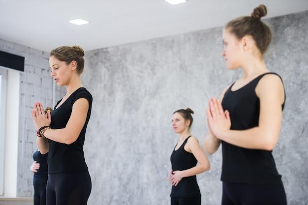 Fitness, meditazione e concetto di stile di vita sano. gruppo di persone che fanno yoga nella posa dell'albero allo studio