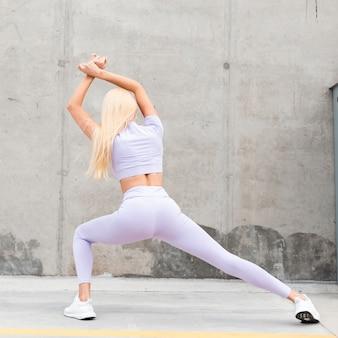 Modello di fitness donna in un bel corpo sportivo snello in abbigliamento sportivo alla moda con scarpe da ginnastica bianche che si estende vicino a un muro di cemento grigio in città, vista posteriore