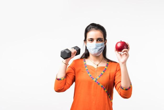 Fitness nel concetto di pandemia - bella ragazza indiana indossa una maschera medica mentre si esercita con il manubrio e mostra la mela