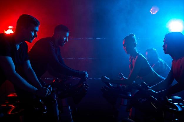 Persone di fitness di fronte a vicenda che esercitano con le biciclette in una palestra. nello spazio blu fumoso. concetto di sport, stile di vita e assistenza sanitaria