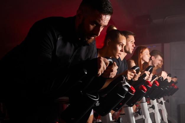 Persone di fitness in fila che si esercitano con le biciclette in una palestra. concetto di sport, stile di vita e assistenza sanitaria