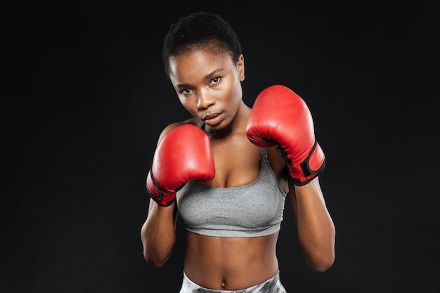 Donna graziosa di forma fisica in guantoni da pugile che combattono sulla parete nera