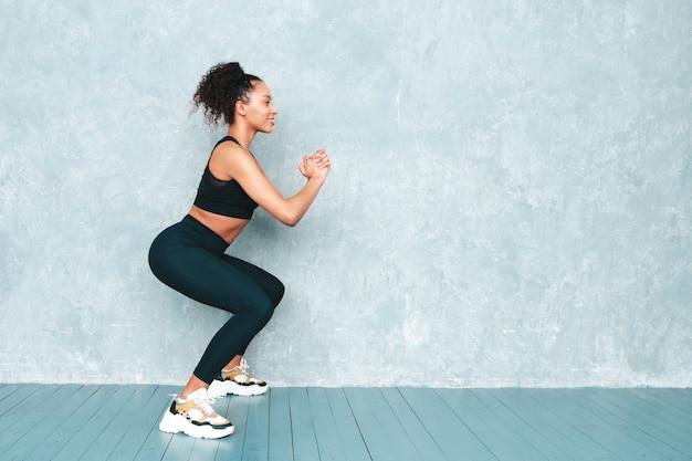 Donna sorridente di forma fisica in abbigliamento sportivo con l'acconciatura di riccioli afro