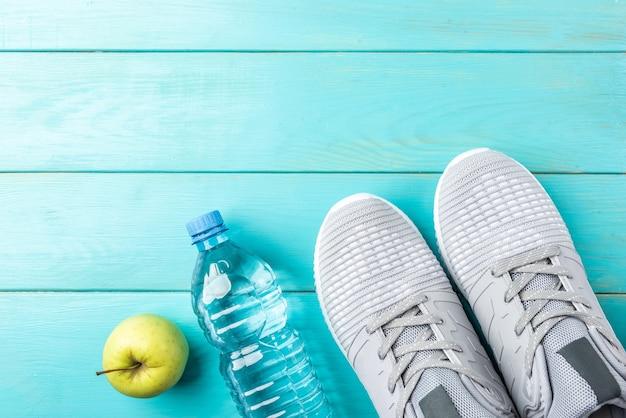 Scarpe da ginnastica fitness, mela verde e bottiglia d'acqua su fondo di legno blu.