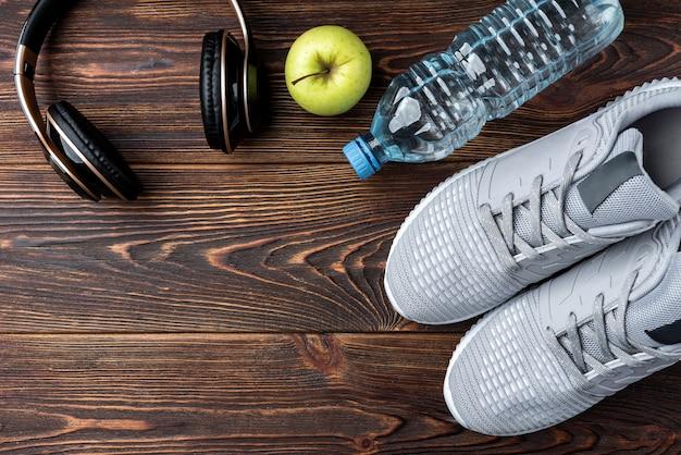 Scarpe da ginnastica fitness, cuffie, mela e bottiglia d'acqua su fondo di legno scuro.