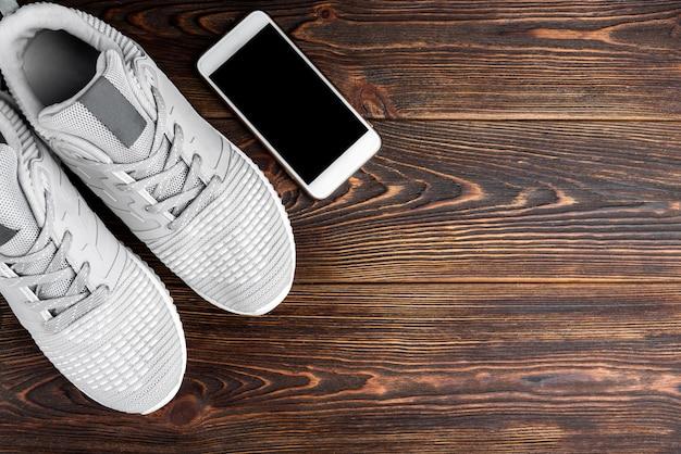 Scarpe da ginnastica fitness e telefono cellulare su fondo di legno scuro.