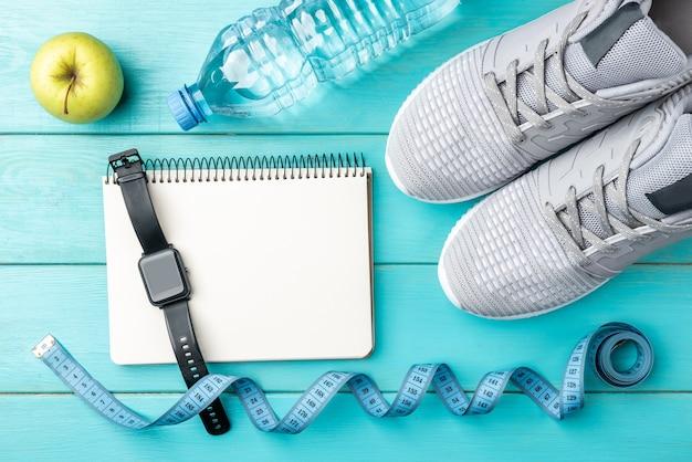 Scarpe da ginnastica fitness, taccuino, mela verde, metro a nastro e bottiglia d'acqua su fondo di legno blu