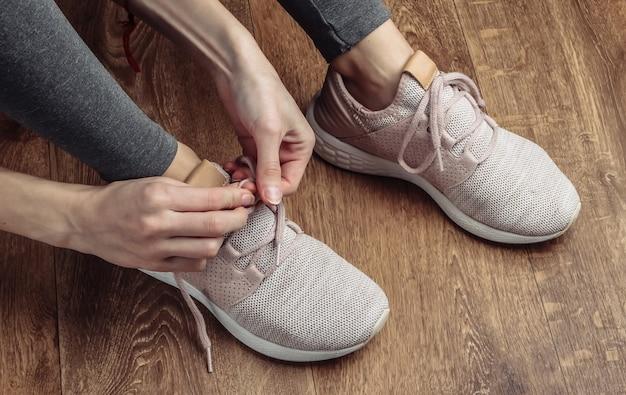 Fitness, concetto di sport. donna che lega i lacci delle scarpe sportive per correre mentre è seduto sul pavimento.